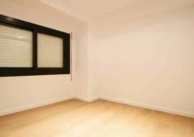 habitacio-parquet-blanc-finestra-alumini-persiana-cantonada